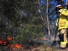 A firefighter works to extinguish a blaze in bushland on Denmans Camp Road.