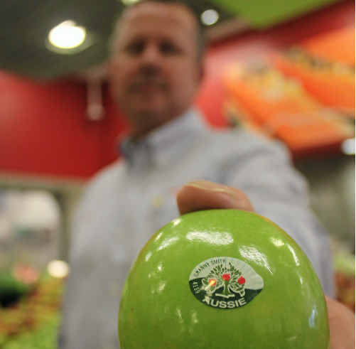 Warwick IGA's Rob Norris displays an Australian apple stocked in the shop.