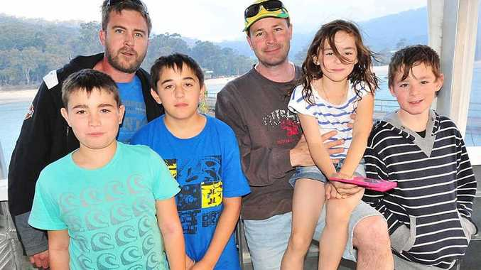 Visitors from Sydney Jason Dillaway and Stephen Grassmayr with children Patrick, Lawrance, Brodie, Lindsay and Isaac leave Fraser Island after their holiday accommodation was evacuated.