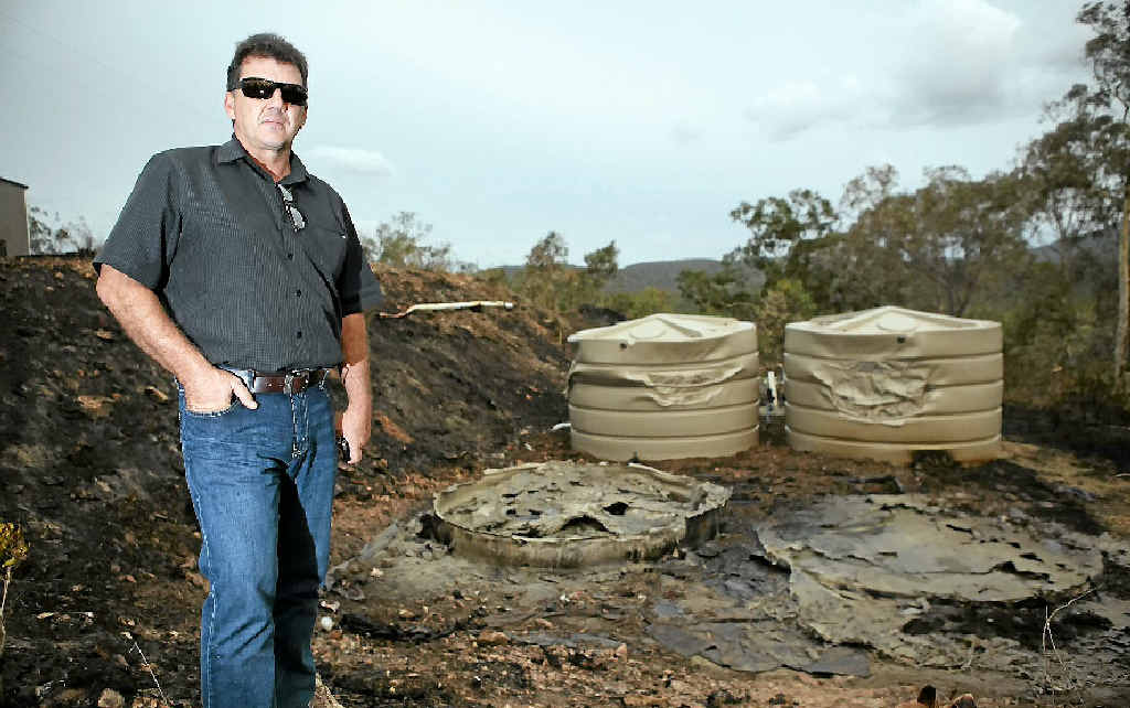 Brian Smith stands above his water tanks that were burnt in the wildfires along Yeppoon Rd over the weekend.