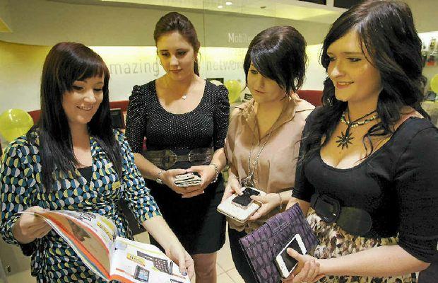 Optus Rockhampton store manager Jodie Ferguson showcasing the new iPhone 4S to Kayla Bruce, Georgia Spry and Rhyanna McKernan.