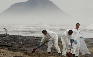 ARMY personnel pictured at work cleaning up the latest oil spill to hit Papamoa Beach from the Rena today.