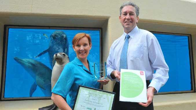 Pet Porpoise Pool marketing manager Angela Van Den Bosch accepts the Pool's carbon neutral award from the regional general manager for Handybin Waste Services, Lee Beckett, as Cindy the sea lion looks on.