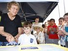 Youngest student Jack White, 5, cuts the cake with 85-year-old former student Dorothy Roach.