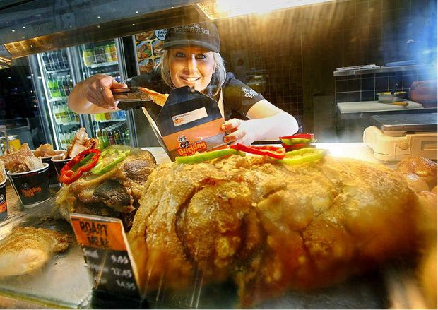 Ashleigh Parfitt serves up some pork crackling at the Bucking Bull carvery at Riverlink Shopping Centre. Bucking Bull has stopped stocking roast lamb in its carvery due to increased meat prices.