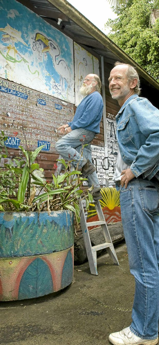 Michael Balderstone (on the ladder) and David Hallett inspect part of a painting by Rolf Harris that was found at the rubbish tip that now hangs outside on a wall at the Nimbin Museum.