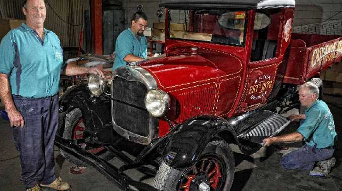 Graham and Nathan Benn and Fred Essex repairing a Model A Ford after it was washed away from the Castlemaine site in the Brisbane floods.