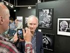 Photographer John Elliott takes a photo of former chief Chronicle photographer Errol Anderson in front of his portrait at the opening of Through The Chronicle Lens photographic exhibition on Saturday.