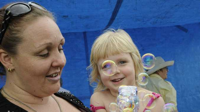Three-year-old sharp-shooter Kaidee Rosentreter discharges her bubble gun from the arms of mum Klara.