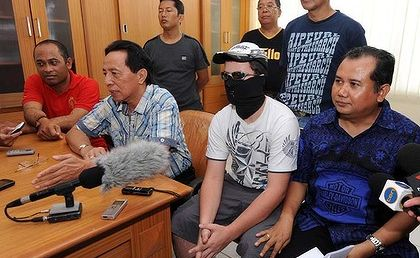 Boy in the mask ... the teenager charged with drug offences in Bali attends a press conference after moving jails yesterday. Photo: Hansel Nashyo