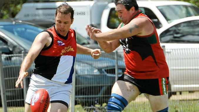 Bundy Brewers' David Ward gets a kick away before Hervey Bay Fruit Bats' Graham Pope has a chance to smother in the AFL Masters Cup.