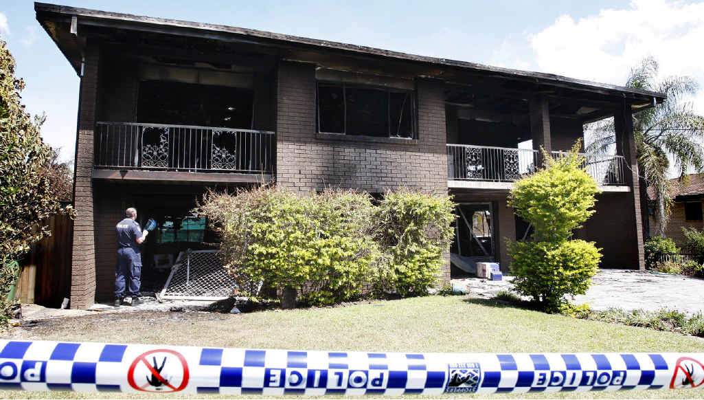 Police and fire investigators inspect the Bundamba house that went up in flames yesterday.