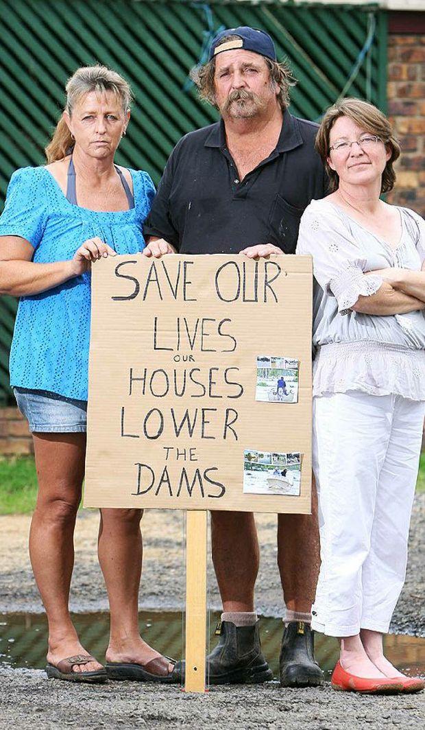 Bundamba Flood Group organiser Dianne Dimitrov, with husband Van Dimitrov and group secretary Erin Cook, are demanding dam levels be reduced.