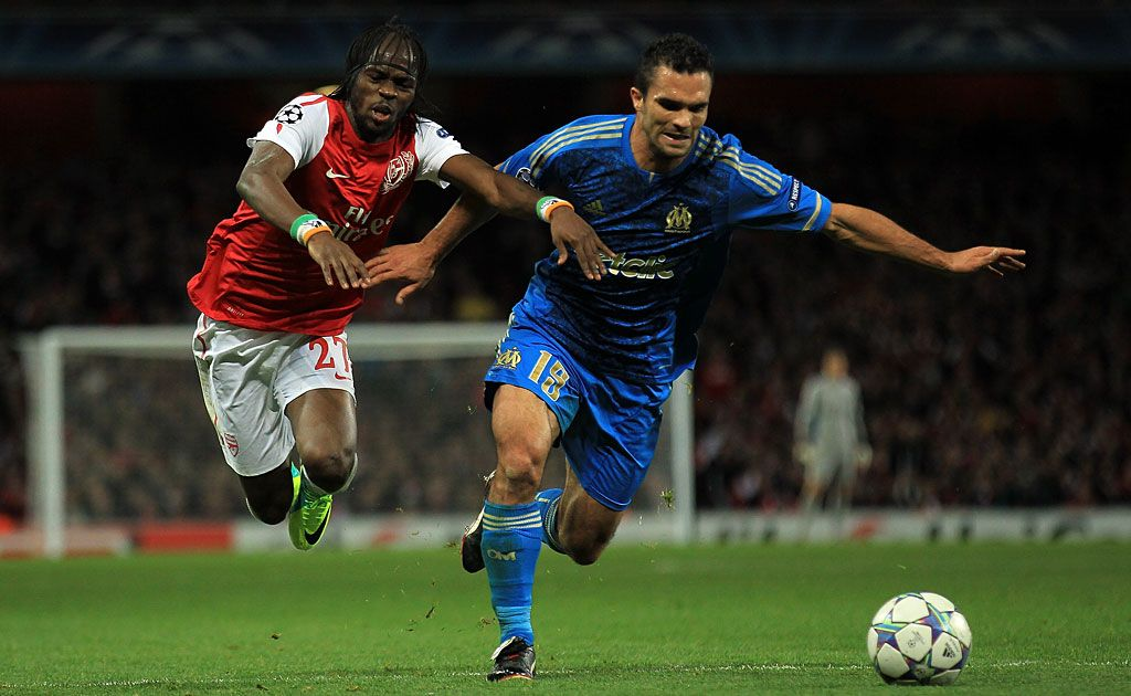 Gervinho of Arsenal battles for the ball with Morgan Amalfitano of Olympique de Marseille during the UEFA Champions League Group F match between Arsenal FC v Olympique de Marseille at Emirates Stadium in London, England.