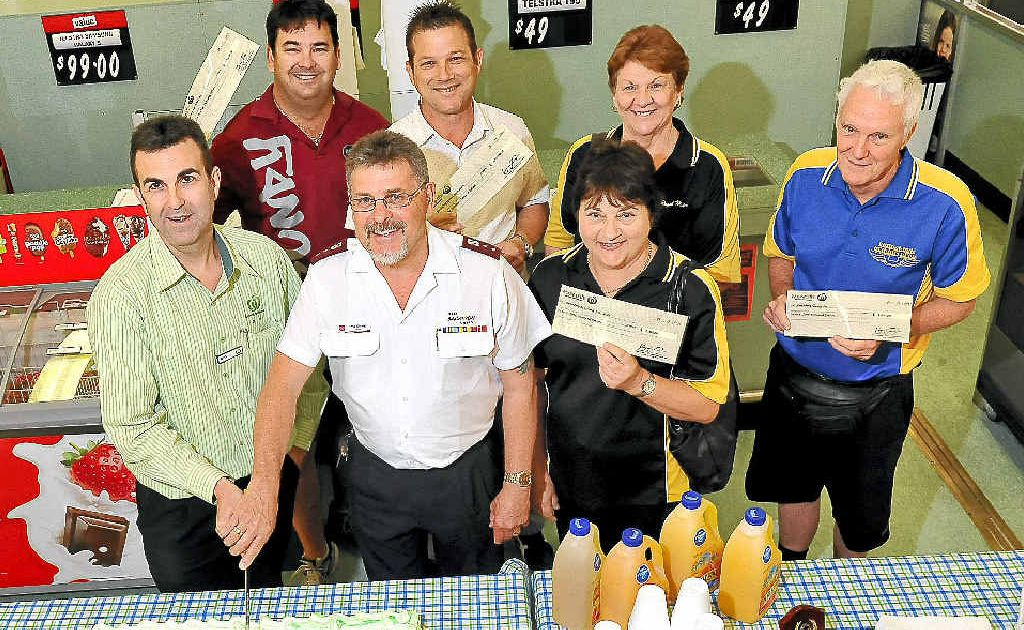 Woolworths Sugarland store manager Ross Henderson and Salvation Army Captain Phil Sharp with donation recipients from Bundaberg basketball, netball and gliding clubs.
