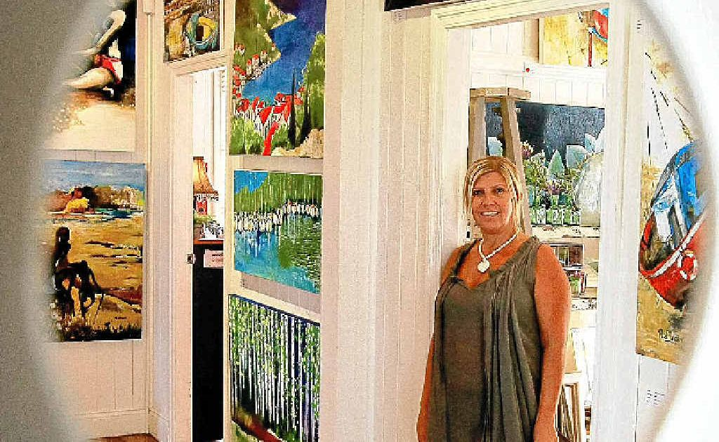 Donna Archdeacon from D'Bar Gallery with some of the paintings by Rosa d'Argent.