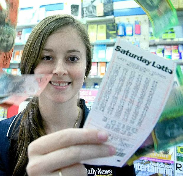 Newton's Newsagency staff member Loren Dalziel with a lotto ticket.