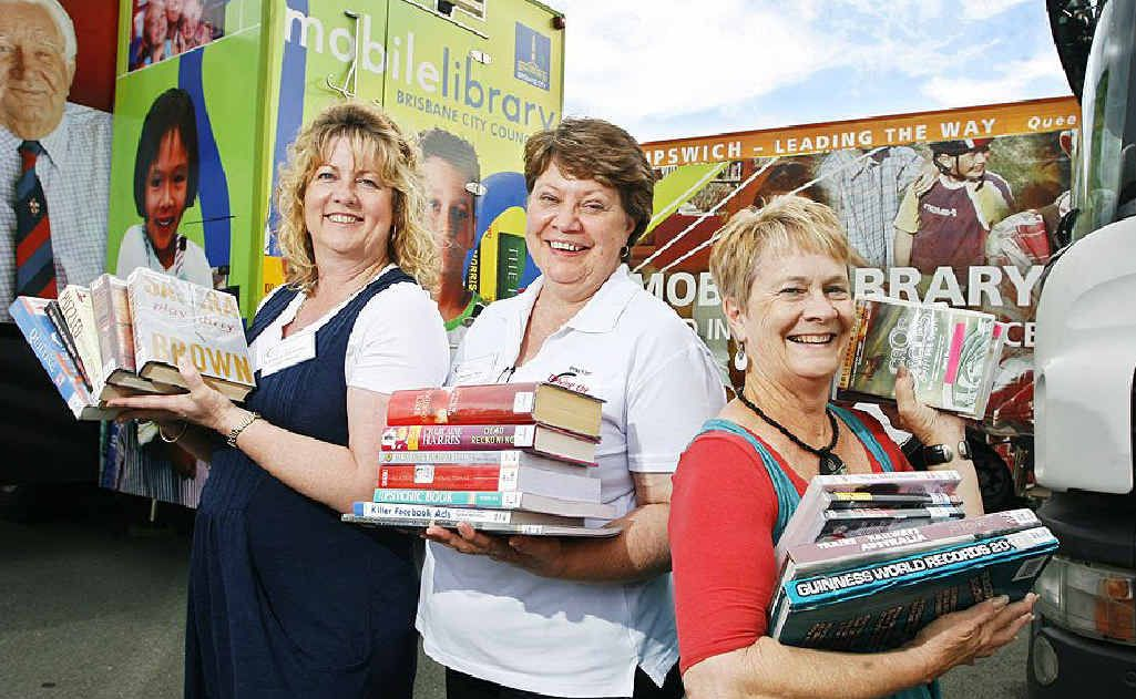 Librarians Margaret Ross from Upper Murray Regional Library, Cheryl Pye from Redbank Plains branch and Margaret Ross from Upper Murray Regional Library gather next to mobile library vans