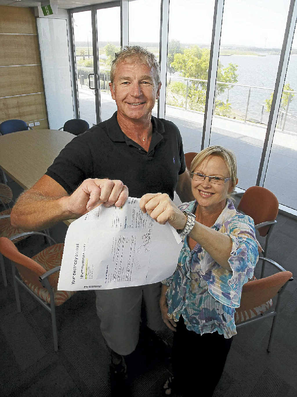 GOODBYE COST: RGD's Ron Grabbe and Tracey Carbis rip up an electricity bill.