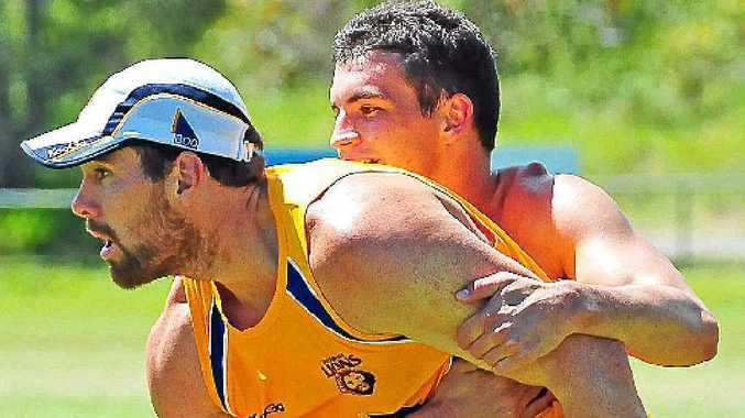Brisbane Lions player Tom Rockliff wraps up Brisbane Lions recruit Ben Hudson as they train at Noosa.