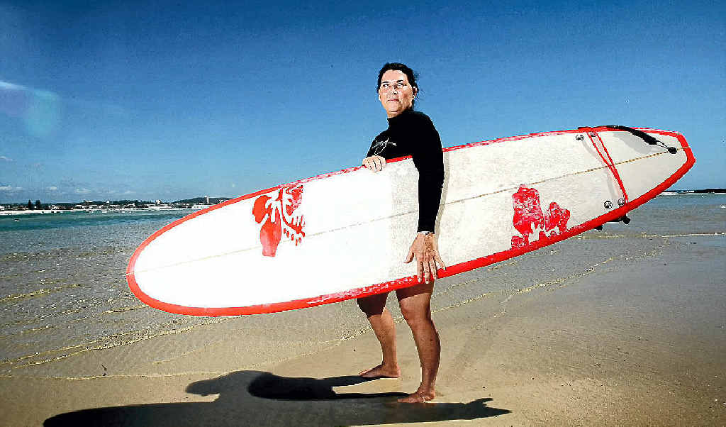 ICONIC BEACH LIFESTYLE: Janine Rawlings at home with her surfboard on Currumbin Beach.