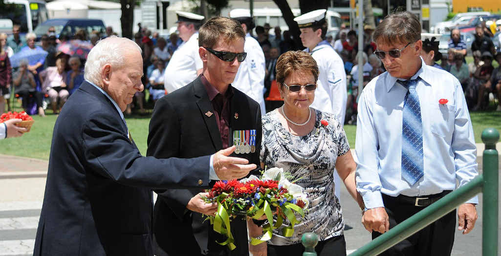 Bob Stretton helps Dale, Linda and Don Birt lay a wreath for the fallen.