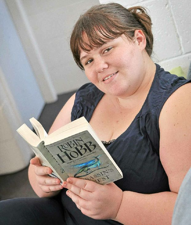 University student Rachel Tait chills out and reads a book. She has trouble balancing work, university and life.