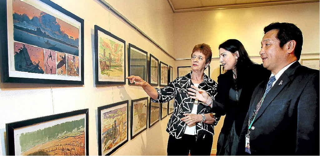 Cr Jan Grew, Casey Marshall and Nao Hirano admiring the anime exhibition.
