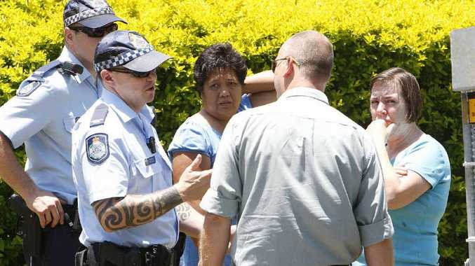Police and animal management officers speak to residents Marilou Mortensen and Robyn Watson at the scene where two dogs mauled a family cat to death.