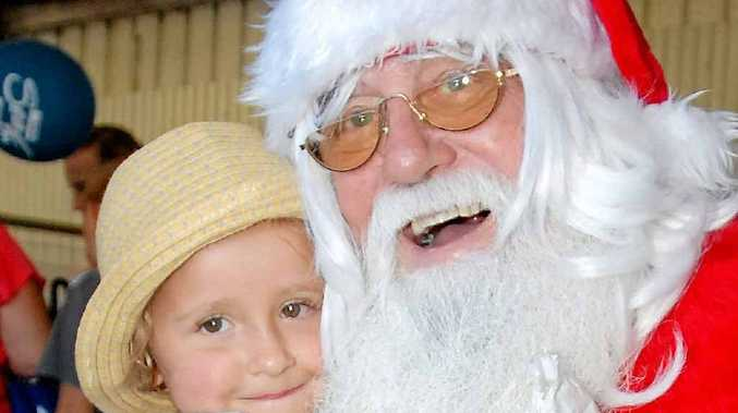 Ruby Vantongren, 4, gives Santa a hug at the Special Children's Christmas Party in Mackay.