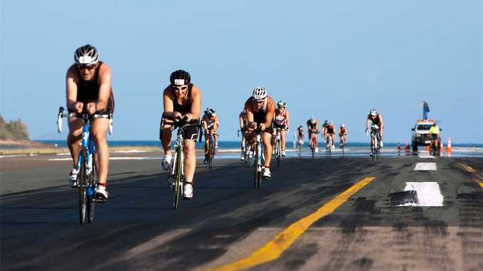 BIKING IT: Competitors race across the runway during the bike leg of the Hamilton Island triathlon.