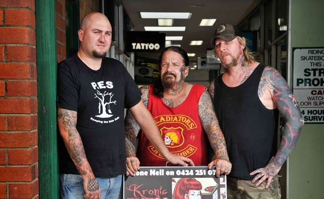 Owners of Kronic Tattoo Luke McLachlan, Bradley Cooper and Neil Overwater with the sign deemed offensive by Clarence Valley Council.