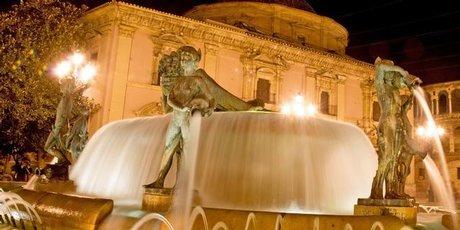 The court convenes by the fountain in the Plaza de la Virgen.