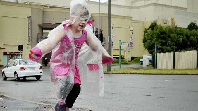 Young Margaret Kretschmer leaps into a puddle outside Grand Central Shopping Centre in Toowoomba this morning.