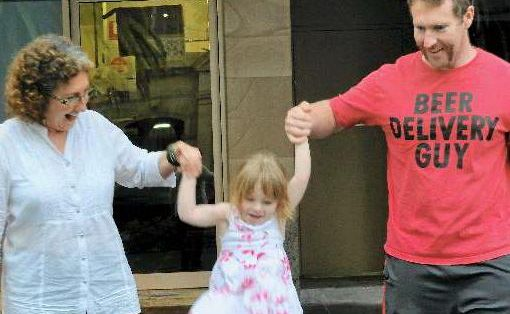 Ariona Laws (in the middle) dodges the puddles after the wet weather with the help of grandma Jan and dad Ken.