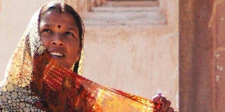 A woman adjusts her sari in the sun.