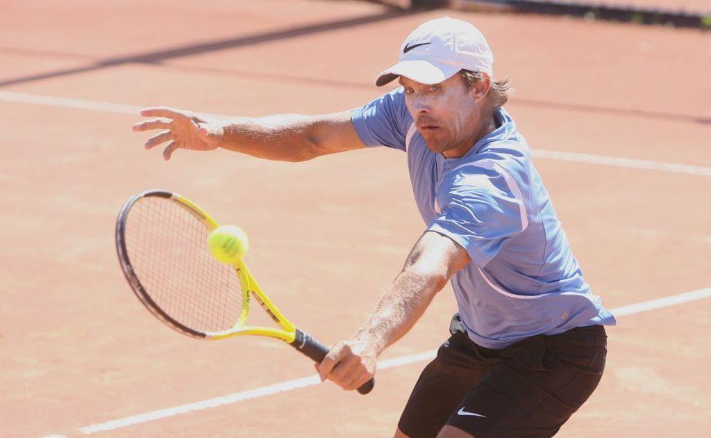 Darren Verrall returns a serve during a top level seniors match player at George Alder Tennis Centre on Saturday.