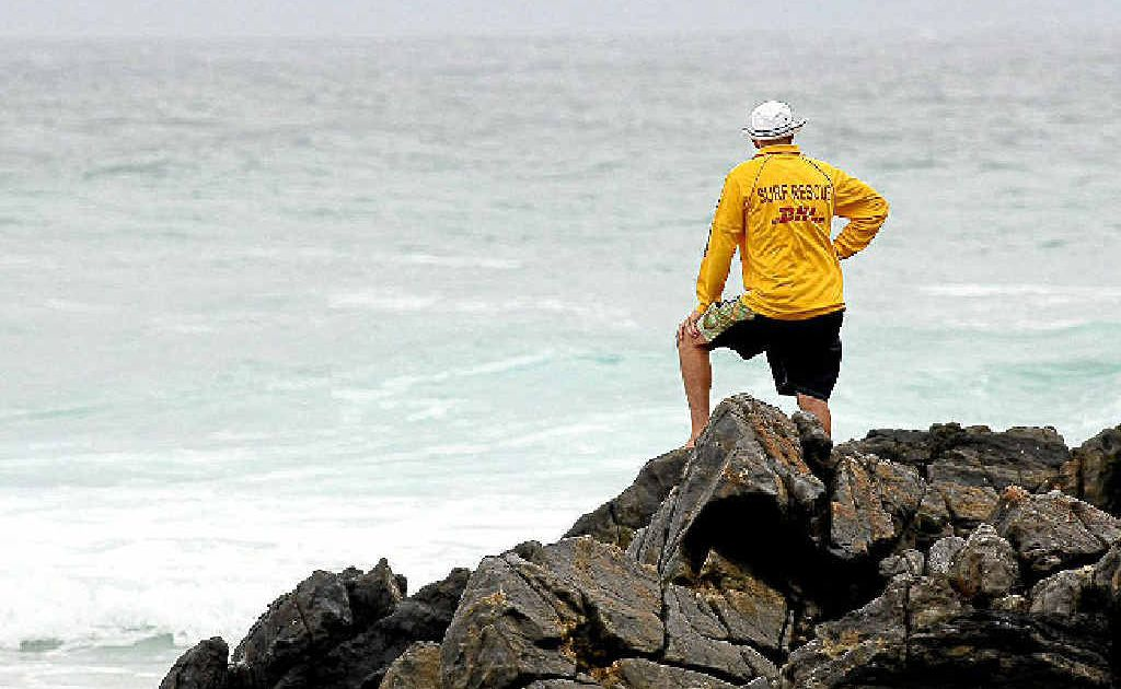 A surf lifesaver assesses the conditions at Cabarita Beach as the search for 16-year-old Lindisfarne Anglican Grammar student Sam Macharia continued.