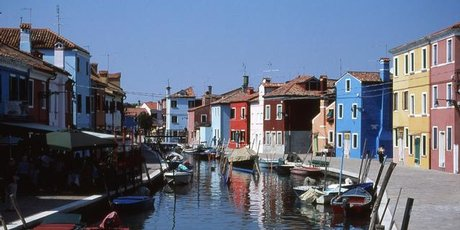 Brightly painted houses reflect in the peaceful canals of Venice's Burano Island.
