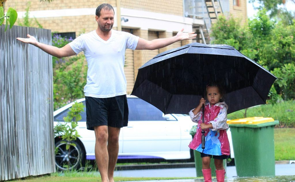 Aaron Abraham and daughter Alliyah, who is escaping the rain under her big umbrella.