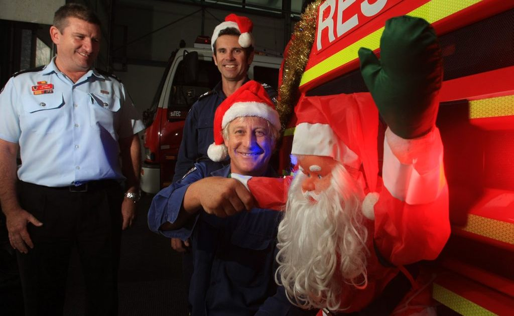 Tweed Fire fights left to right- Inspector Jeff Roche, Senior Fire fighters Neil King and Peter Sutherland with Santa on the front of the truck Photo Blainey Woodham / Tweed Daily News