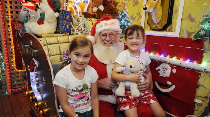 Mia, 7, and sister Lucy Russell, 4, spending a little time with Santa at Pat Kennedy's house on Riverview Avenue in West Ballina.