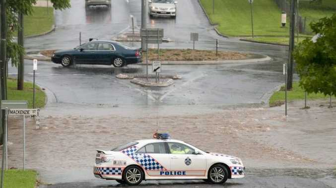 Police close the intersection of Mackenzie and South sts as water from East Creek flows over the road, Saturday, December 10, 2011.