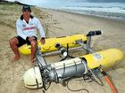 Lifeguard Peter Cherry with the sophisticated submersible vehicle washed up on Glen Eden Beach at North Peregian.
