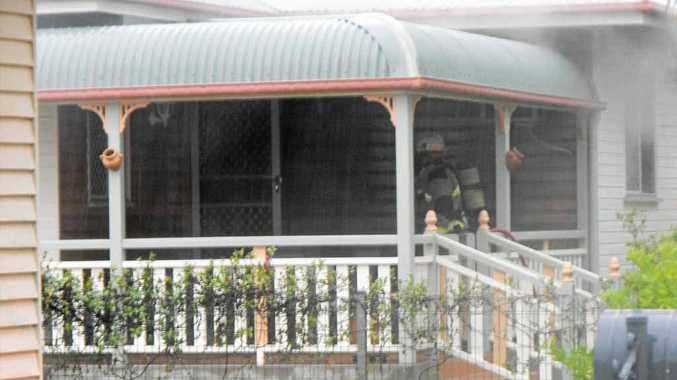 Fire crews work to extinguish a blaze that started in the kitchen of house on May St, Walkervale, after cooking oil ignited.