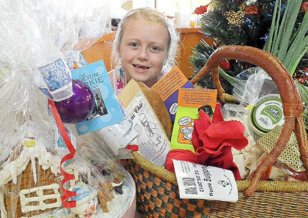 Sari Conti, whose great grandparents were Hunchy (near Palmwoods) pineapple farmers, enjoys the family fun of making a gift hamper at the Big Pineapple Growers and Fine Food Markets.