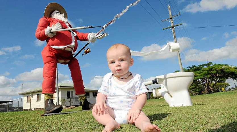 Xavier Kelly with his nana's roadside Santa, who is placed in different poses every day to entertain passing motorists.