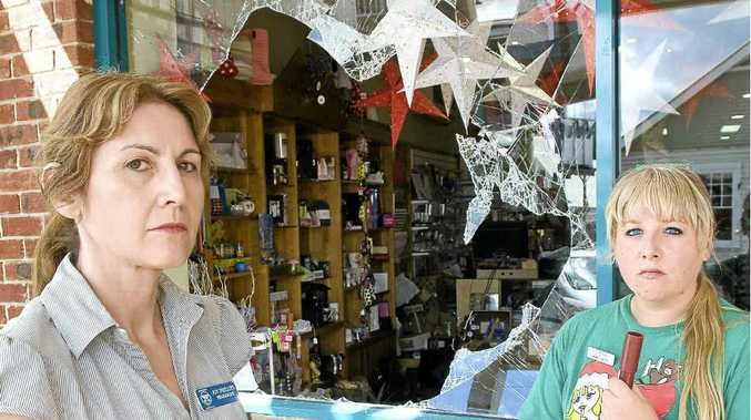 Main Street Pharmacy proprietor Joy Phillips and Steffi Hawke clean up the damage after the shop was raided for drugs.