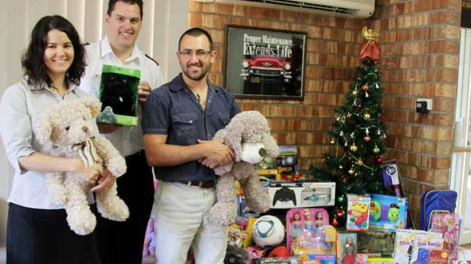 Bethany Wagstaff, Lieutenant Richard Day and Dr Duanne Spiccia with the mountain of toys donated by patients in the Toys for Treatment day at Alive Chiropractic.