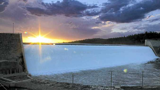 The sun sets on Paradise Dam as recent rain sends about 700ML spilling over its wall a day.